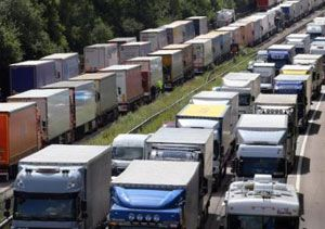 image: UK road haulage freight truck park lorry Operation Stack migrant camp Jungle Calais