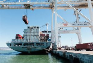 image: US Port of Oakland cargo shipping line container crane hybrid gantry tyred marine terminal freight